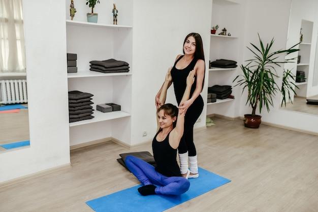 L'insegnante di pilates sta aiutando la giovane donna a fare stretching