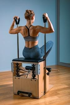 Pilates donna in un riformatore facendo esercizi di stretching in palestra. concetto di fitness, attrezzature speciali per il fitness, stile di vita sano, plastica. copia spazio, banner sportivo per la pubblicità.