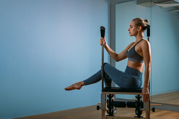 Donna di pilates in un riformatore facendo esercizi di stretching in palestra