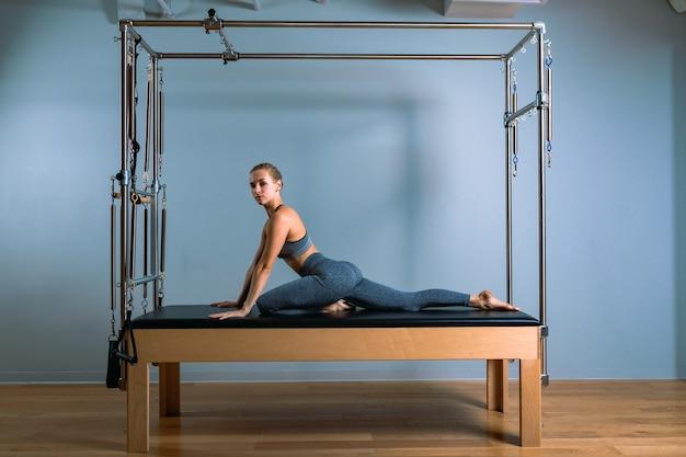Donna di pilates nel teaser del riformatore esercizio in palestra al chiuso