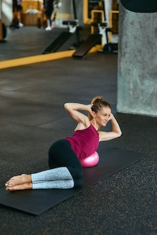 Allenamento pilates. giovane donna caucasica in abbigliamento sportivo sdraiata sul tappetino da yoga in palestra e facendo esercizi addominali, usando una piccola palla fitness sport, allenamento, benessere e stile di vita sano