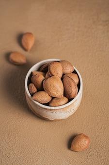 Mucchio di mandorle noci in una ciotola su uno sfondo marrone. noci fresche nel loro guscio.