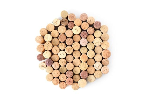 Pila di tappi per vino usati assortiti a forma di cerchio isolato su priorità bassa bianca.
