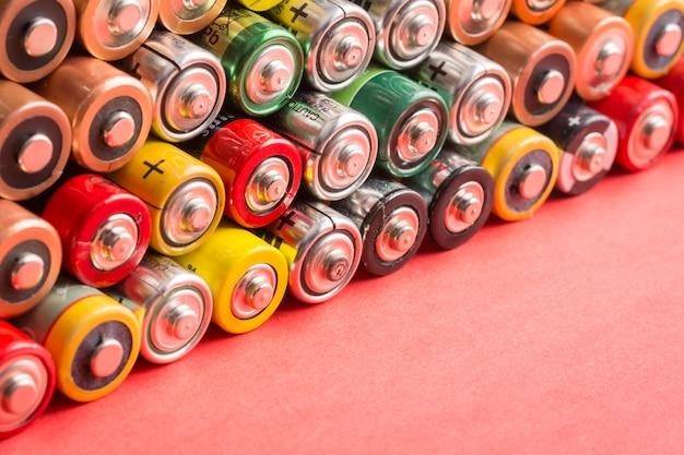 Pila di batterie, accumulatori di diversi produttori giace su uno sfondo rosso