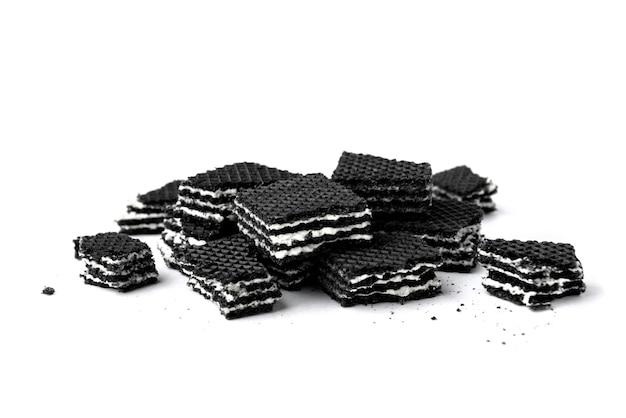 Mucchio di wafer neri isolati su sfondo bianco.