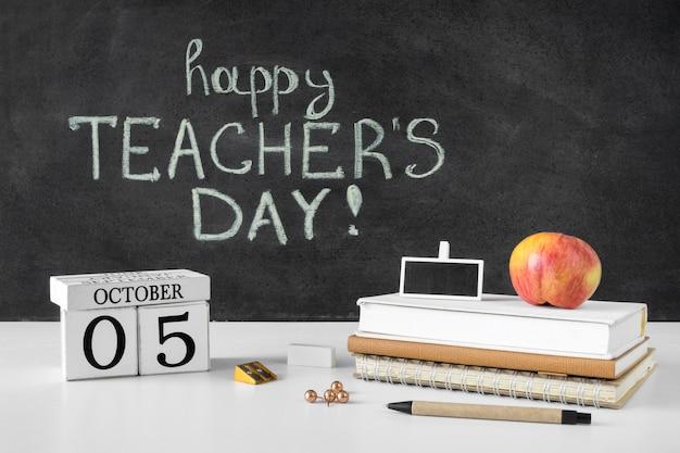Pila di libri e concetto di giorno dell'insegnante felice della mela