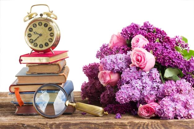 Pila di libri e orologio con fiori lilla e rosa isolati su bianco