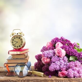 Pila di libri e orologio con fiori lilla e rosa sulla tavola di legno