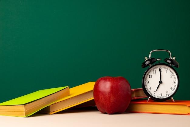 Pila di libri e mela rossa sulla scrivania. torna al concetto di scuola