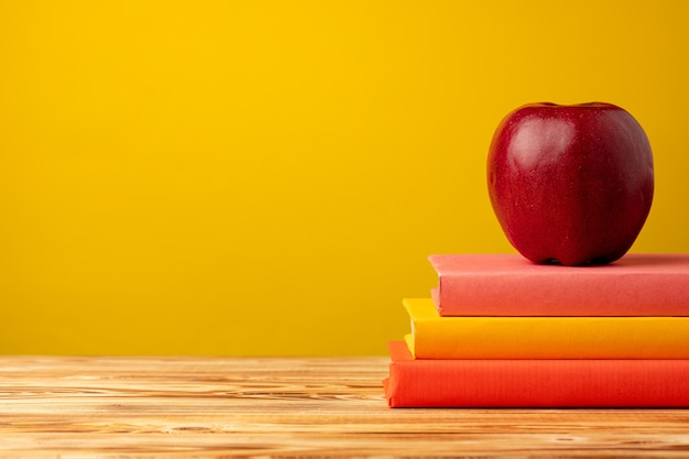 Pila di libri e mela rossa sulla scrivania
