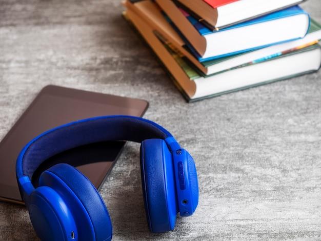Pila di libri con le cuffie sul tavolo