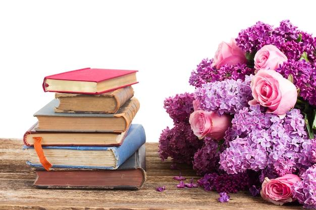 Pila di libri con fiori lilla e rosa isolati su bianco