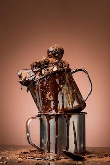 Mucchio di cioccolato rotto in cerchi di metallo e spray al cioccolato caldo