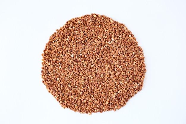 Un mucchio di chicchi di grano saraceno su uno sfondo isolato