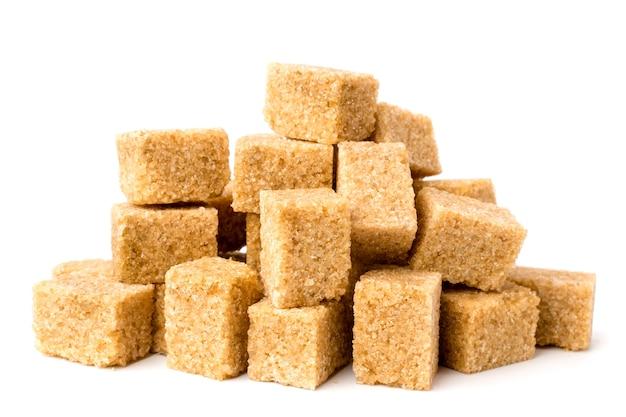 Un mucchio di zucchero di canna non raffinato su bianco, primo piano. isolato.