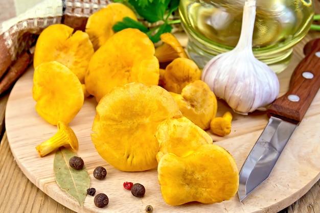 Un mucchio di gallinacci, decanter con olio vegetale, coltello, tovagliolo, aglio e spezie su uno sfondo di assi di legno