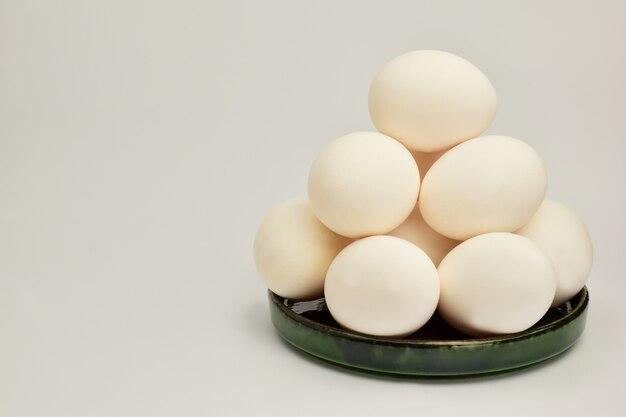 Un mucchio di uova di gallina giace in un piattino di ceramica c'è un posto a sinistra per un'iscrizione