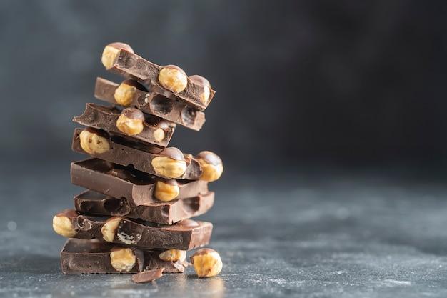 Mucchio di cioccolato con noci sul tavolo grigio, da vicino