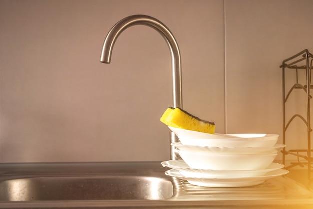 Una pila di piatti puliti con una spugna nel lavello della cucina, foto del concetto di lavoro domestico