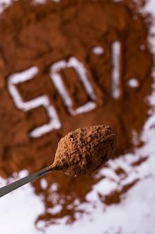 Mucchio di cacao in polvere con un cucchiaio, 50% di cioccolato al cacao