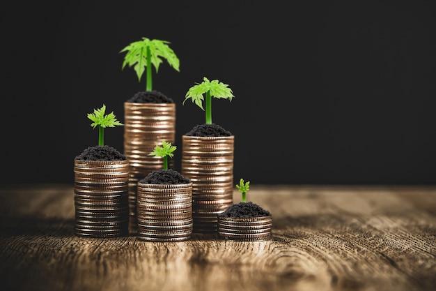 Pile di monete sono impilate in una forma di grafico con alberi che crescono per idee di risparmio di denaro e assicurazione di pianificazione finanziaria.