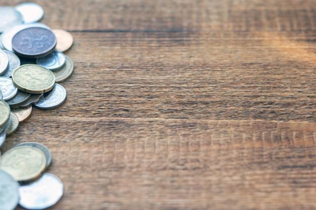 Un mucchio di monete su un tavolo in legno con copia spazio
