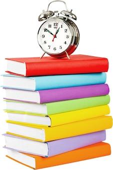 Pila di libri colorati e sveglia in cima su sfondo bianco