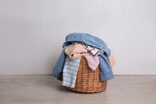 Un mucchio di vestiti colorati cade da un cesto di vimini della lavanderia su uno sfondo chiaro