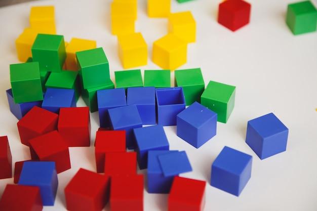 Mucchio dei cubi variopinti sulla tavola bianca. sviluppo iniziale di un concetto di bambino.
