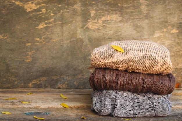 Mucchio dei vestiti caldi variopinti su legno