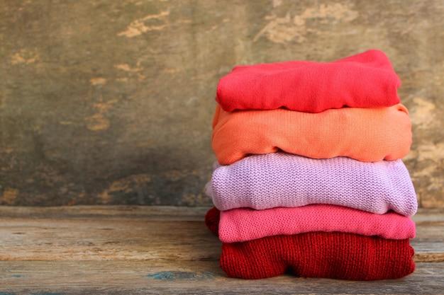 Pila di vestiti caldi colorati su legno