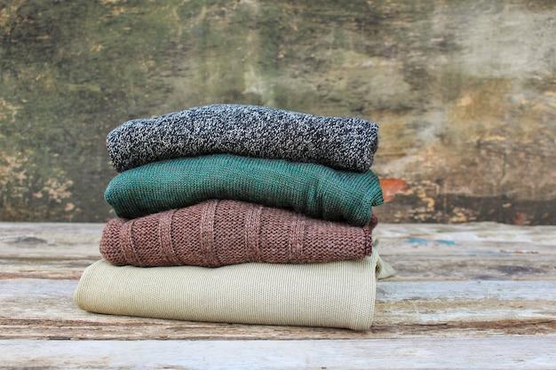 Mucchio di vestiti caldi variopinti su fondo di legno. immagine tonica.