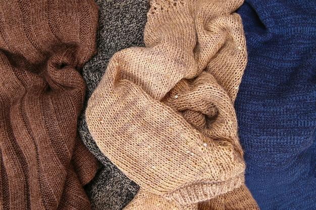 Mucchio di vestiti caldi colorati su fondo di legno. vista dall'alto. disposizione piatta.