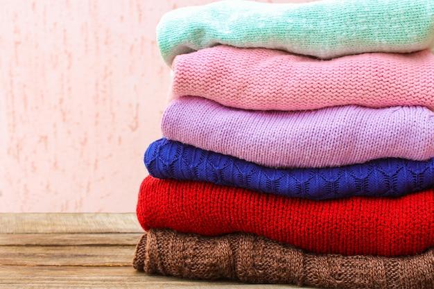 Pila di vestiti caldi colorati su fondo di legno.