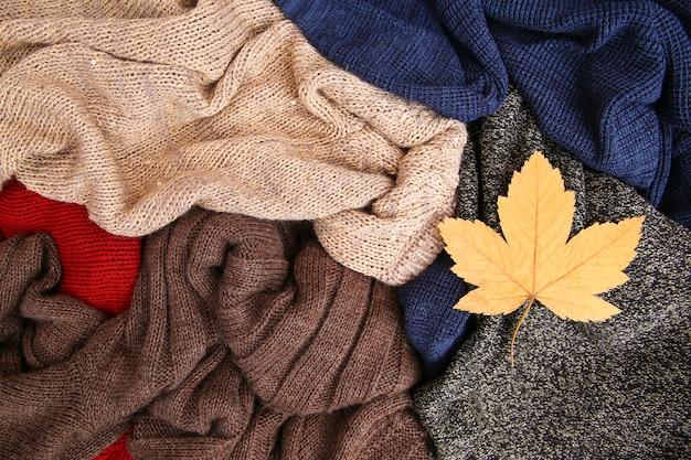 Mucchio dei vestiti caldi variopinti su fondo di legno
