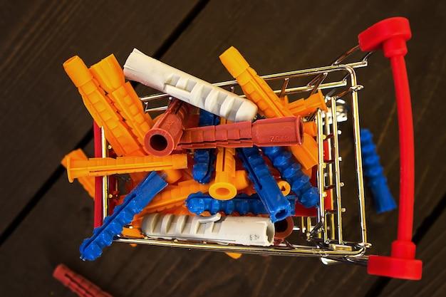 Mucchio di tasselli in plastica colorati nel carrello della spesa in miniatura. shopping per il concetto di riparazioni..