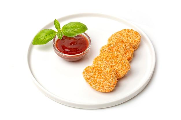Un mucchio di pepite di pollo cotte in un piatto con salsa di pomodoro, isolato su sfondo bianco