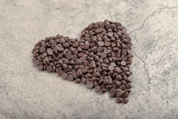 Pila di gocce di cioccolato fondente gocce disposte come un cuore.