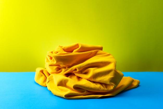 Mucchio di vestiti sporchi di lavanderia sul tavolo blu sfondo giallo chiaro.