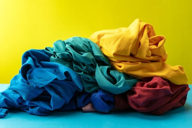 Mucchio di vestiti sporchi lavanderia sul tavolo blu sfondo giallo chiaro.