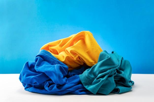 Mucchio di vestiti sporchi di lavanderia sul tavolo bianco sfondo blu.