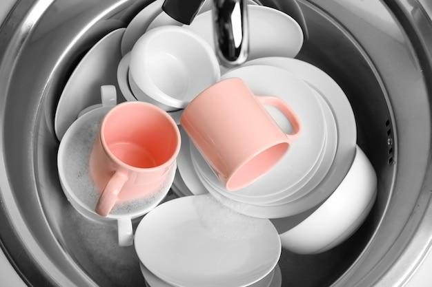 Pila di piatti in primo piano del lavandino