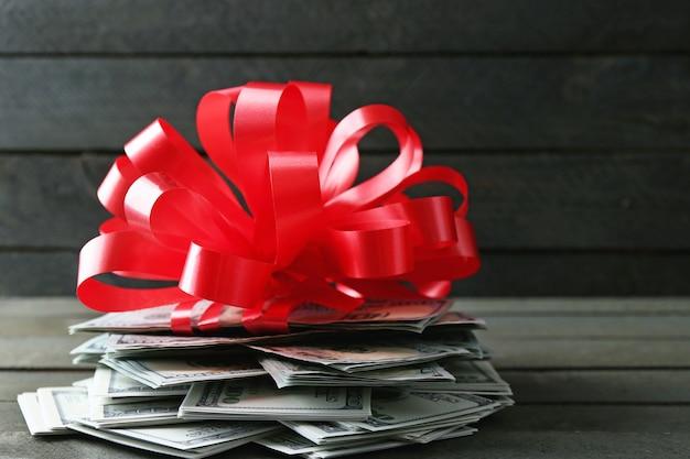 Pila di dollari con fiocco come regalo sulla tavola di legno