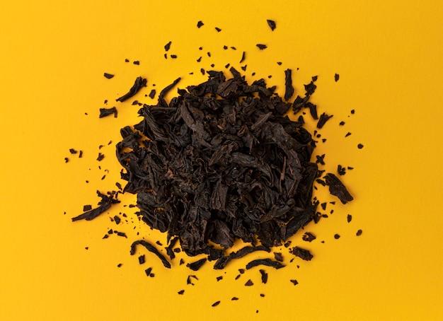 Pila di foglie di tè nero secco su sfondo giallo, vista dall'alto