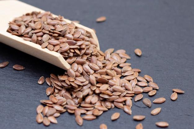 Mucchio di lino o semi di lino in un cucchiaio di legno su uno sfondo di pietra nera. sfondo scuro concetto di semi di lino.