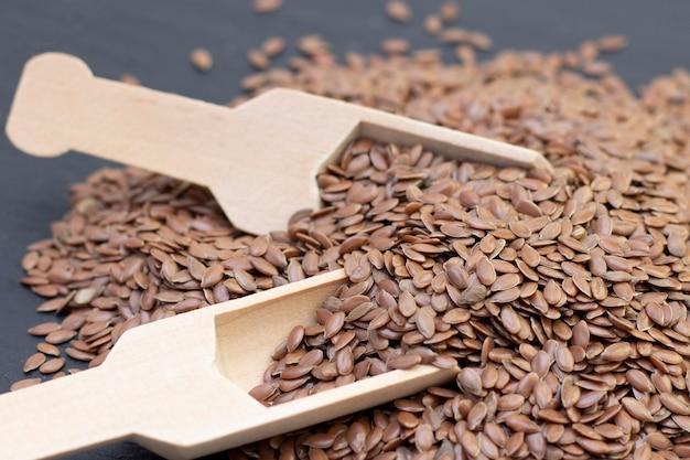Un mucchio di semi di lino o di lino in un cucchiaio di legno su uno sfondo di pietra nera