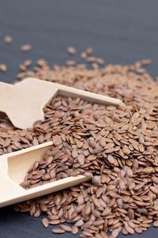 Pila di lino o semi di lino in un cucchiaio di legno su uno sfondo di pietra nera.