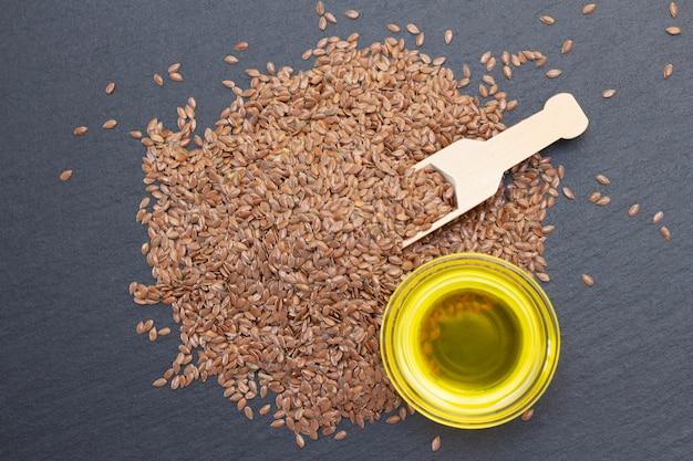 Un mucchio di semi di lino e olio di lino in un cucchiaio di legno su uno sfondo di pietra nera