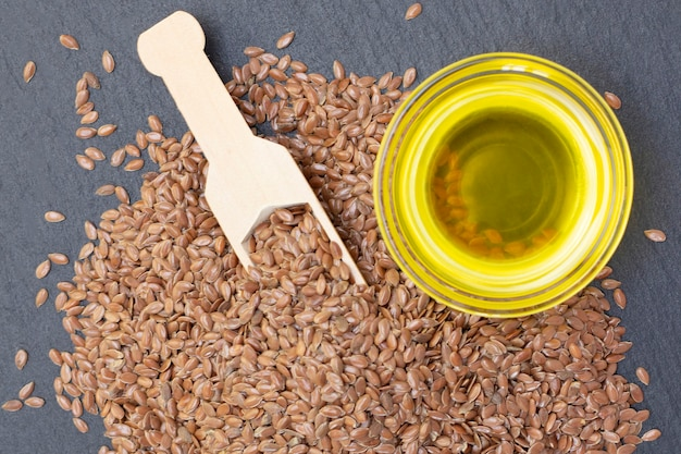 Un mucchio di semi di lino e olio di lino in un cucchiaio di legno