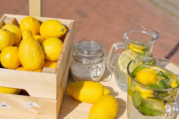 Pila di limoni freschi in una scatola di legno in piedi da brocche di vetro con fette di agrumi e foglie di menta piperita e vaso con zucchero in piedi sul tavolo